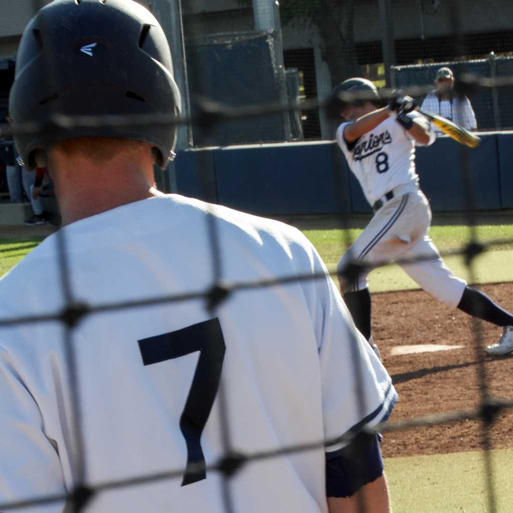 Warriors outfielder Jonny Palmer, 7, waits on deck as Warriors infielder Jack Canady, 8, swings at a pitch during the Warriors Feb. 22 home game against Imperial Valley College. The Warriors won the game 13-3, bringing their season record to 4-6.