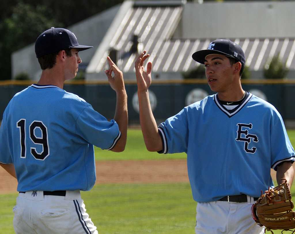 Alex Navarrete, pitcher for the Warriors baseball team, bumps hands with fellow pitcher Colin Nelson as he comes off the field after striking out a San Bernardino Valley College player for the final out in the top of the third inning of the Warriors Feb. 16 game. The Warriors went on to win the game, 12-3.