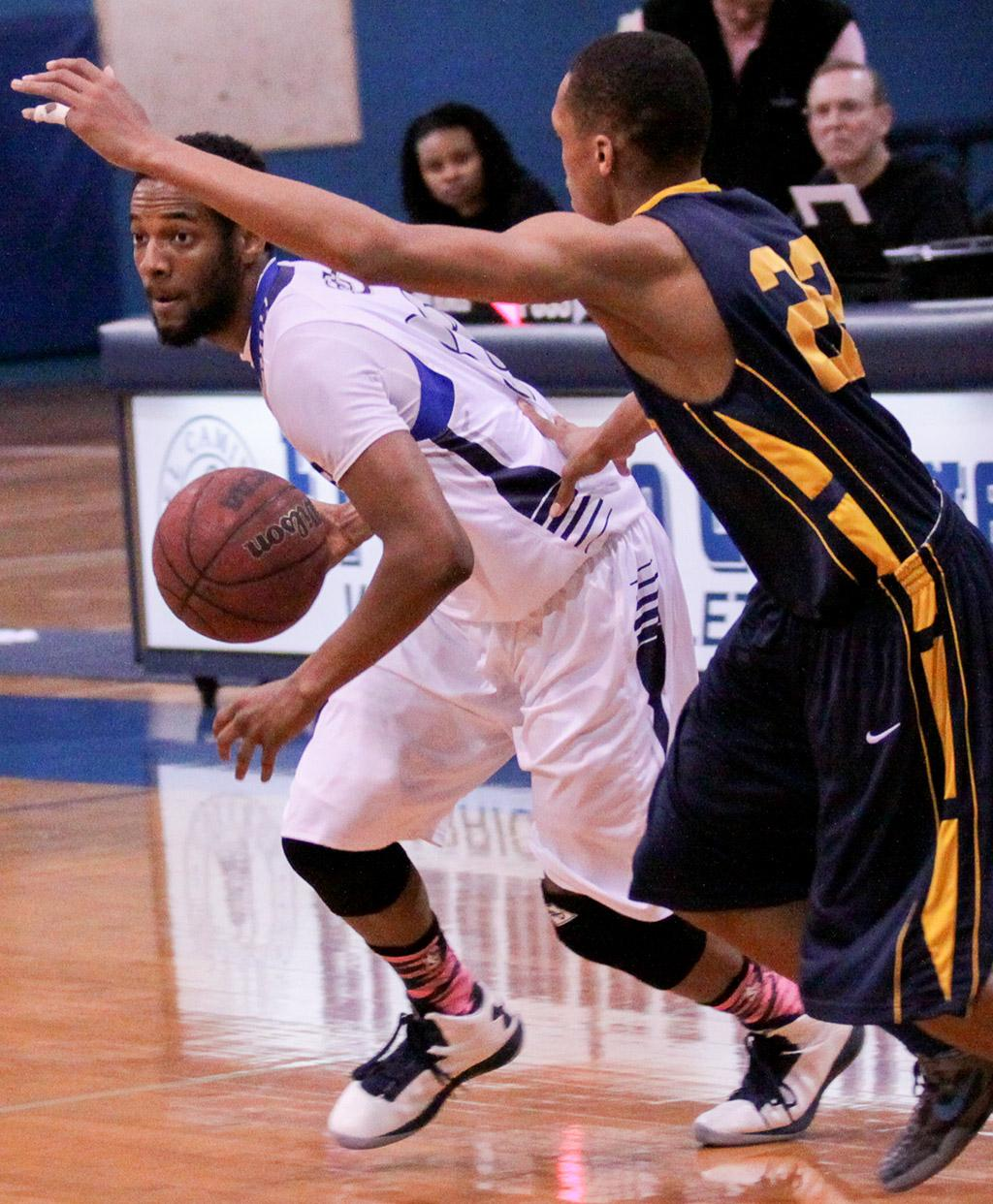 Marcus Clark, freshman shooting guard for the Warriors, drives past Donnell Drain, point guard for the Los Angeles Harbor College Seahawks, during the first half of the Warriors Feb. 15 game. The Warriors spent the majority of the game trailing the Seahawks in points and ended up losing, 60-70.