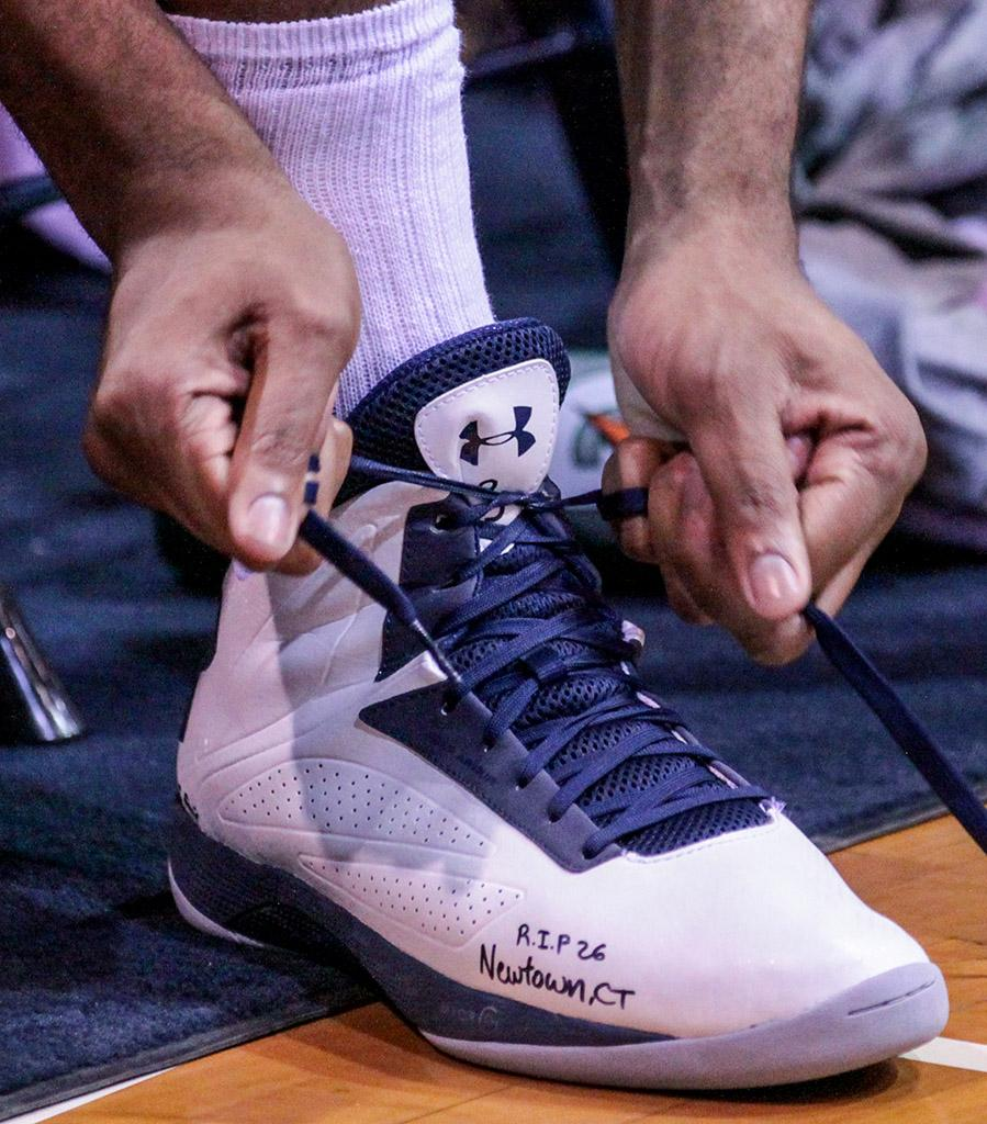 """A player from the Warriors men\'s basketball team takes a moment to retie his shoe, which has the message """"R.I.P 26 Newtown, CT"""" written on the side, during the teams Feb. 15 game against Los Angeles Harbor College Seahawks. The Warriors lost the game, 60-70."""