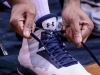 """A player from the Warriors men's basketball team takes a moment to retie his shoe, which has the message """"R.I.P 26 Newtown, CT"""" written on the side, during the teams Feb. 15 game against Los Angeles Harbor College Seahawks. The Warriors lost the game, 60-70."""