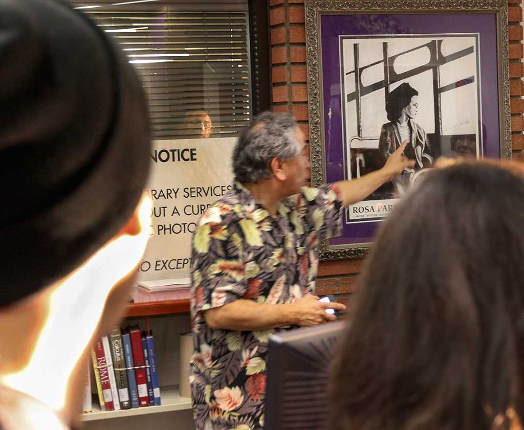 Ed Martinez, librarian, talks to students and faculty about a picture of civil-rights-activist Rosa Parks during the Feb. 15 reception for the 2013 Black History Month Exhibit located in the lobby of the Schauerman Library. The exhibit opened Feb.1 and will be on display until Feb. 29.