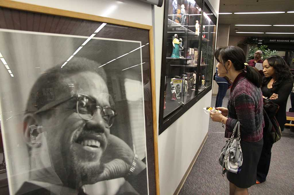Visitors to the 2013 Black History Month Exhibit, located in the lobby of the Schauerman Library, look at a collection of caricature dolls of prominent African Americans as well as a collection of biography's about some of those same individuals during the Feb. 15 reception for the exhibit. The dolls and books belong to Maria Brown, history professor, who also curated the exhibit.