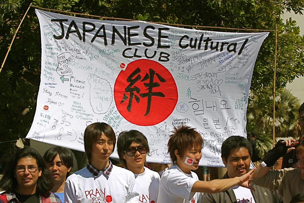Students gather in front of a sign to which students left personal messages for the families who are suffering from the Tsunami that hit Japan.
