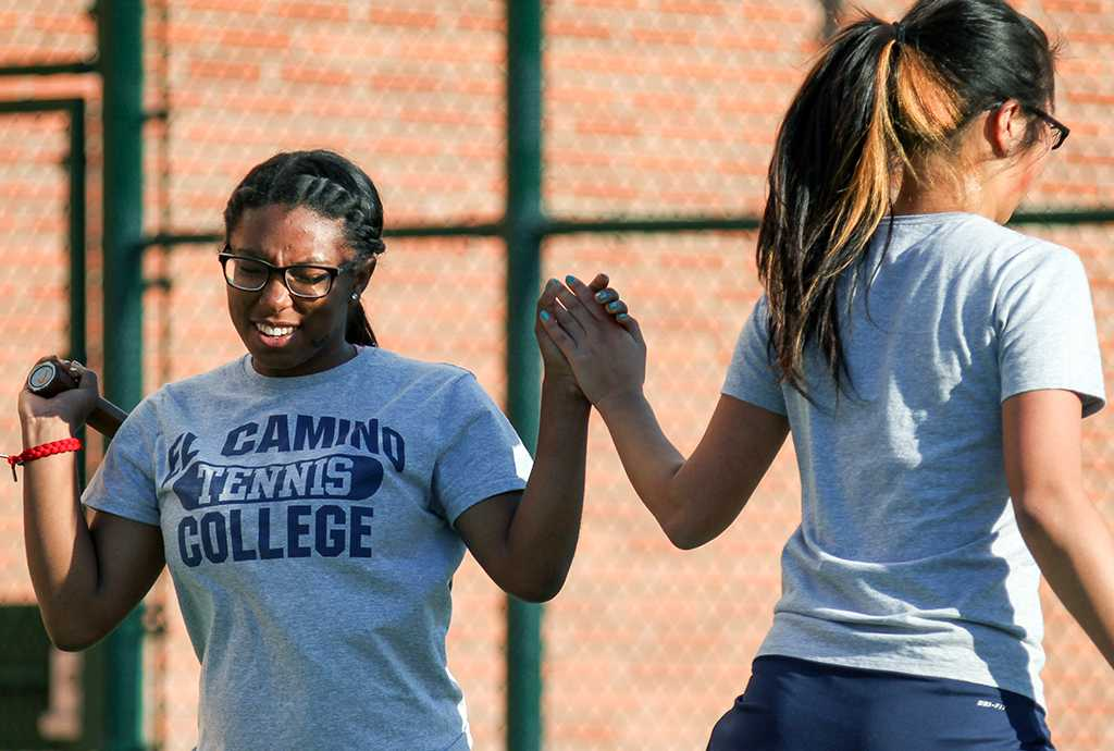 Warriors women's tennis team players Heather Shambrey, 18, left, and Karin Endo, 21, right, high five after winning a set during their Feb. 21 doubles match against Long Beach City College players.  The match was part of the women's tennis tournament with LBCC that was hosted at EC. The Warriors women's tennis team won the tournament, taking all nine matches.