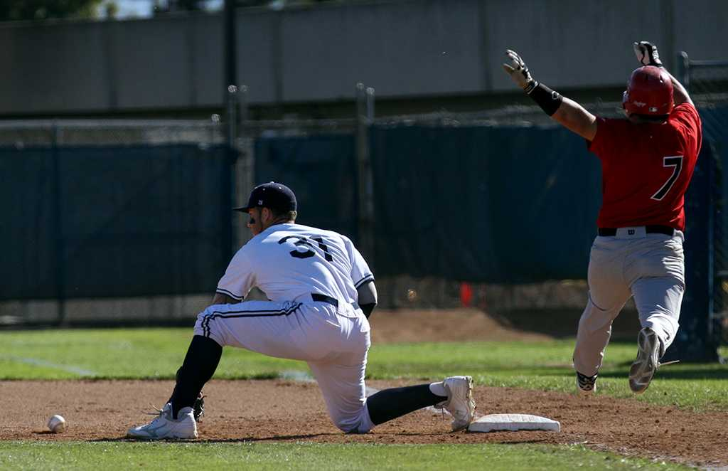Sean Issac, pitcher and utility player for the Warriors, waits for the baseball as as Eric Garcia, infielder for the Imperial Valley College Arabs, leaps towards first base  during the Warriors Feb. 22 home game against Imperial Valley College. The Warriors won the game 13-3, bringing their season record to 4-6.