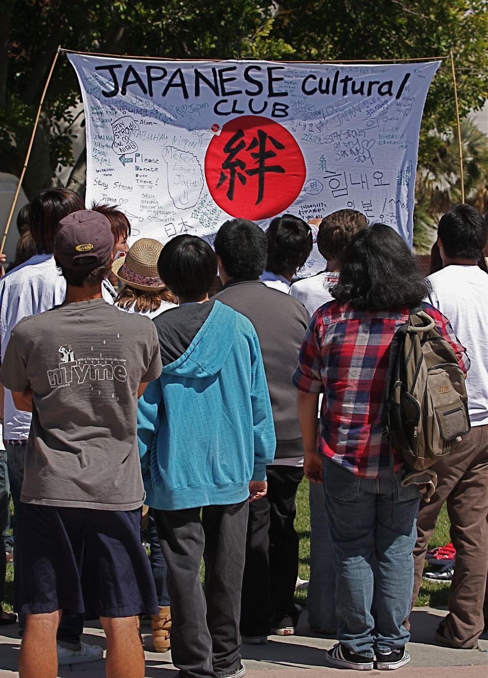 Students gather in front of a flag which students wrote personal messages to reach the families who suffered the terrible Tsunami which hit Japan.