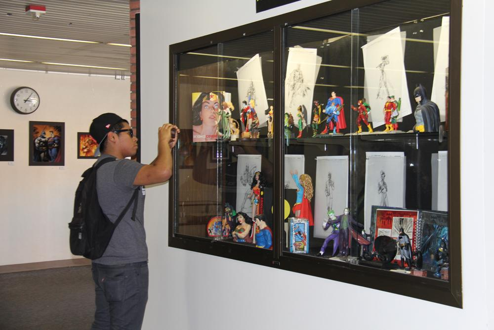 Danny+Gutierrez%2C+23%2C+business+major%2C+snaps+a+few+photos+of+superhero+figurines+and+sketches+as+part+of+the+%22Shadows+of+American+Popular+Culture%22+exhibit+in+the+Schauerman+Library.