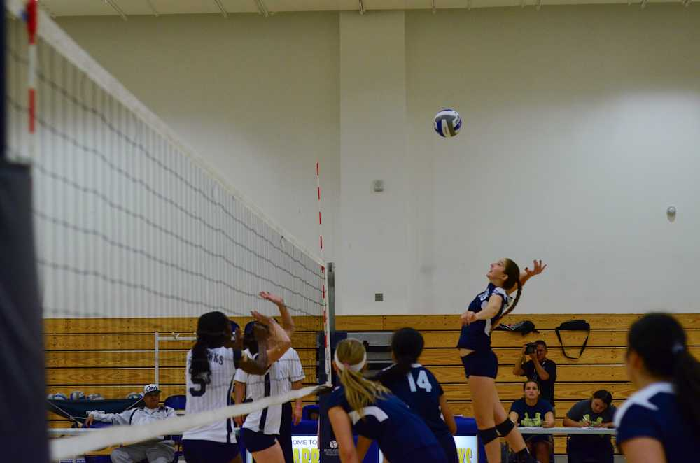 Freshman+outside+hitter+Laynie+Thompson+leaps+high+into+the+air+to+set+herself+for+spiking+position.Photo+credit%3A+John+Ruiz.