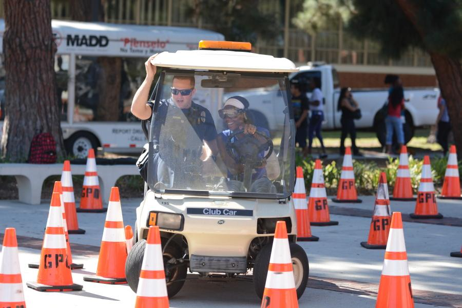 Shadera Woodland, 18, physical therapy major, steers a golf cart while wearing drunk goggles as ECPD Officer Matt Ryan holds on while guiding Woodland at the DUI Awareness Fair on Wednesday. ECPD hosted the event for students to learn about the dangers of impaired driving. Photo credit: John Fordiani