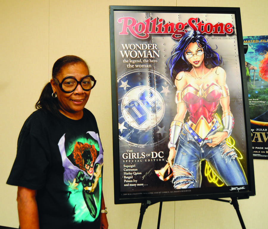 Maria Brown, a history professor at EC, died Wednesday night. Brown was deeply involved in both Black History Month and Comic Book Day events. Here, in a photo taken last month, she stands next to her Wonder Woman Rolling Stone poster in her classroom. Photo credit: Amira Petrus
