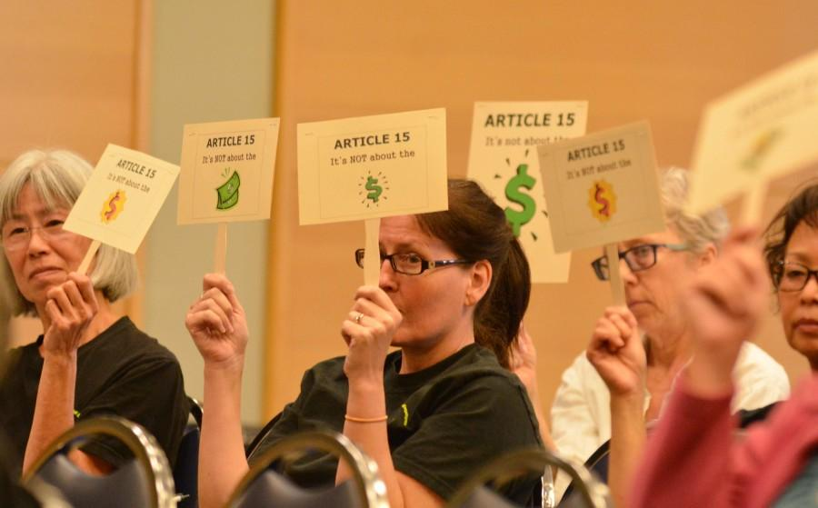Members of the El Camino Classified Employees union hold signs about article 15 at the Monday board of trustees meeting. The classified employees union hasn't seen an adjustment in their cost of living since 2013. Photo credit: John Fordiani