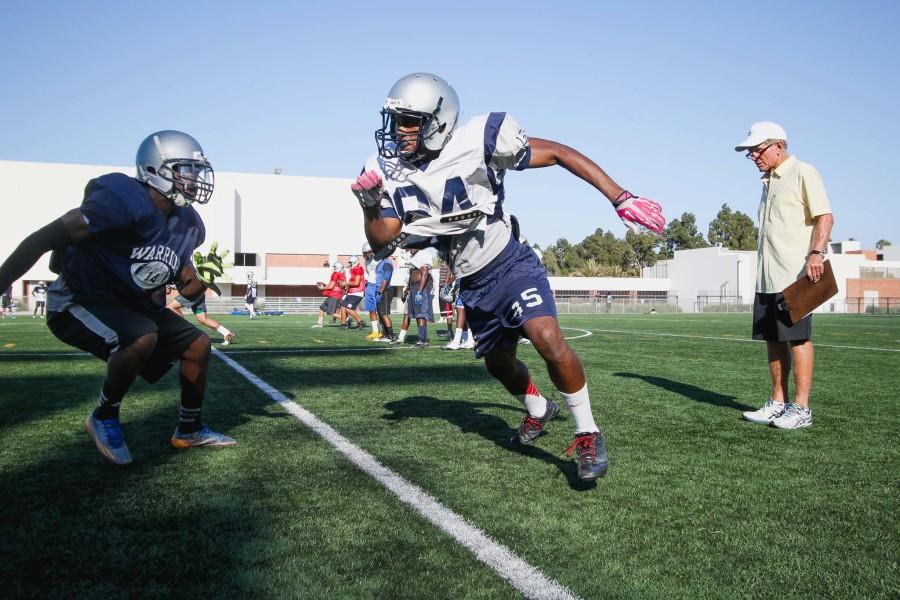 The+Warriors+football+team+practices+drills+on+the+field+as+Coach+Featherstone+watches+the+potential+wide-receivers.+Photo+credit%3A+Jorge+Villa