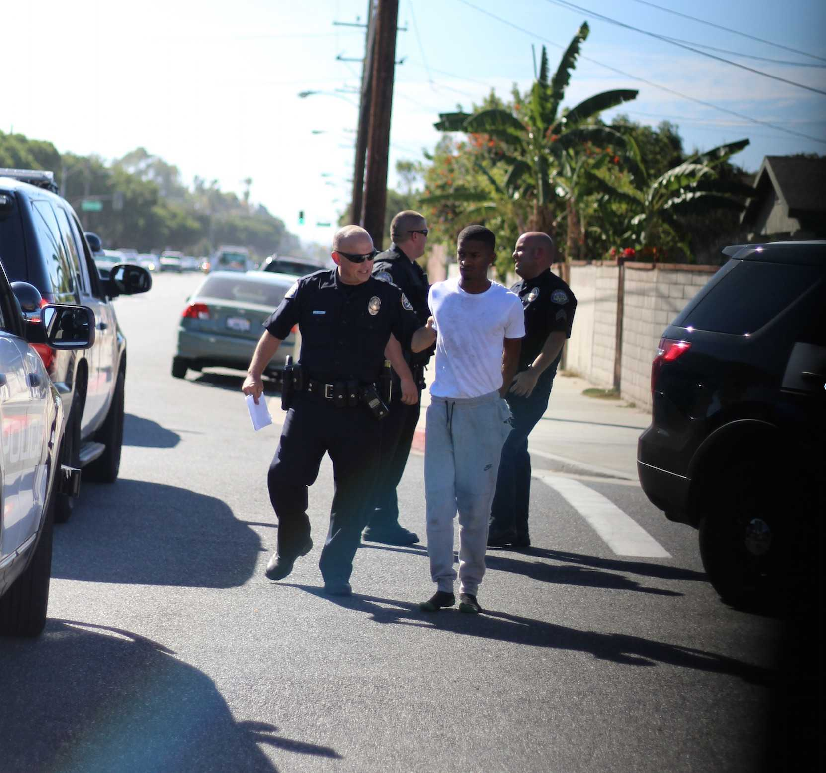 Officer escorts alleged burglary suspect to the back of the squad car. Photo credit: Jo Rankin