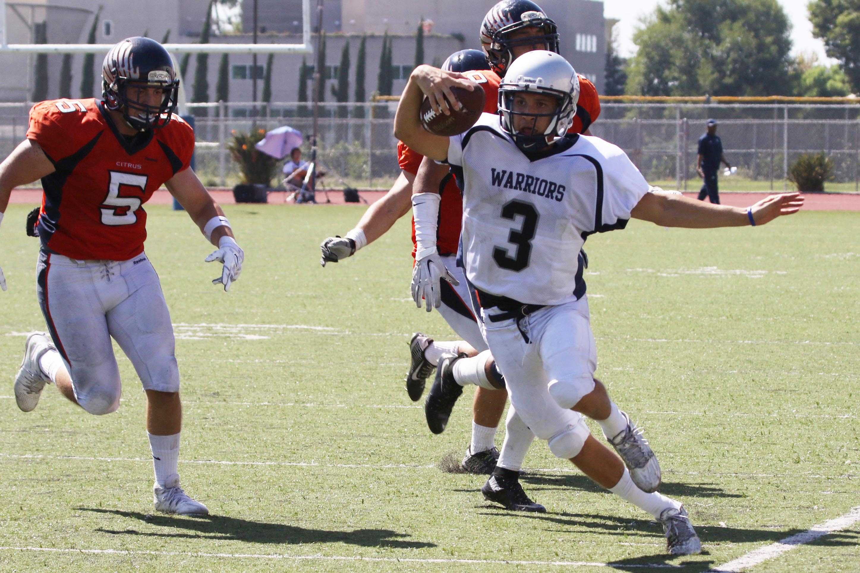 Quarterback Jorge Hernandez  makes a play with a run up field during Saturday's game at Citrus College. The Warriors defeated the Owls 23-20. Photo credit: Jackie Romano
