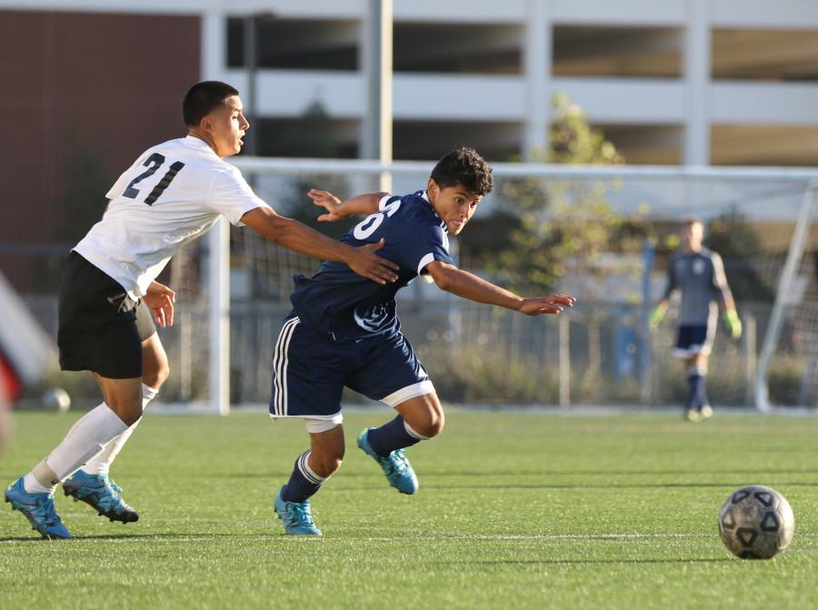 Freshman forward Jorge Gutierrez(16) looks to make a pass upfield while being defended by a Long Beach City player. The Warriors lost to the Vikings, 3-1, during a home game on Friday, Oct. 30. Photo credit: Jo Rankin