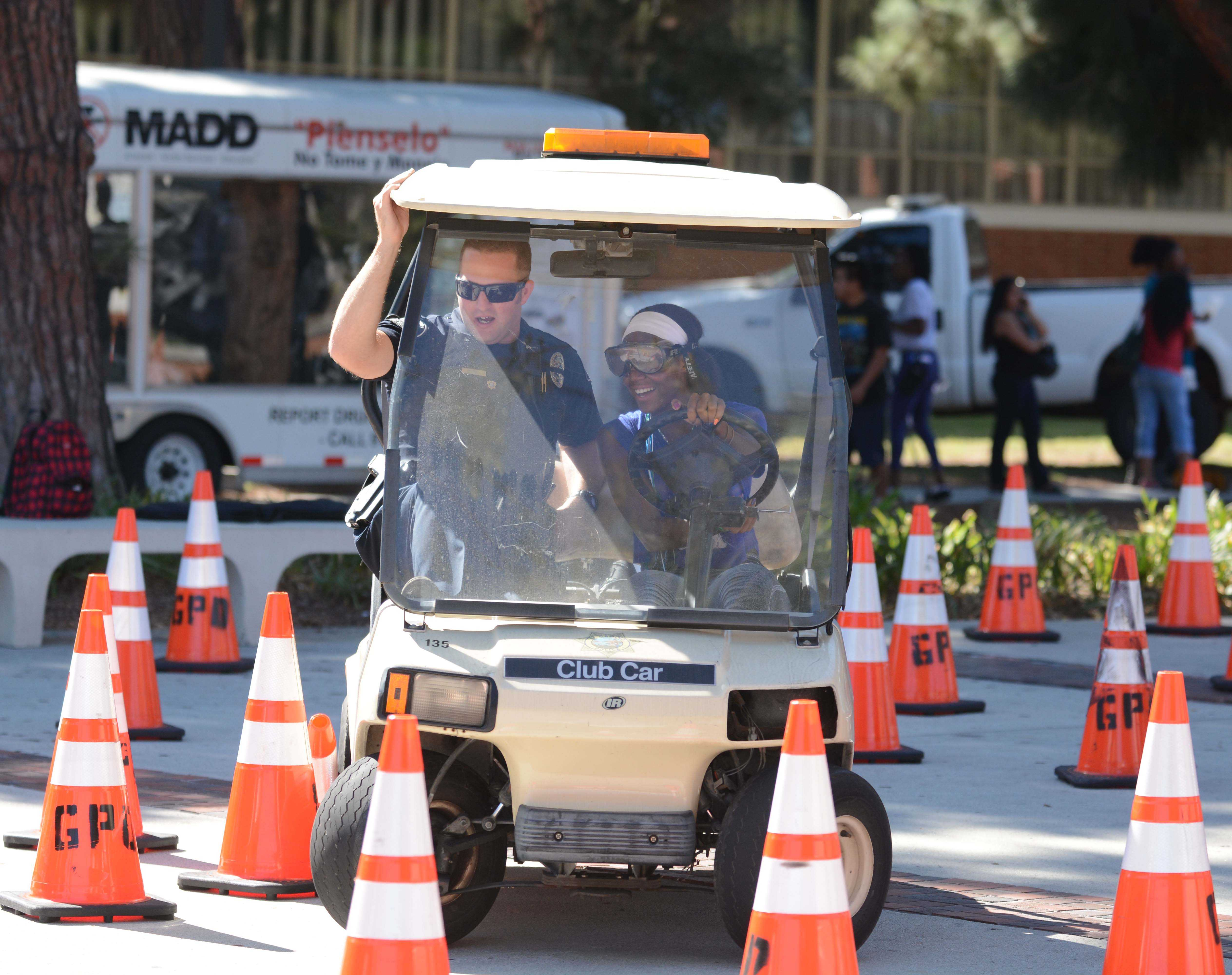 Shadera Woodland, 18, physical therapy major, steers a golf cart while wearing drunk googles as EC Police Officer Matt Ryan holds on while guiding Woodland at the 2014 DUI awareness. ECPD will be hosting the 15th annual DUI awarrness fair on Thursday Oct. 29 near the Library Lawn. Photo credit: John Fordiani