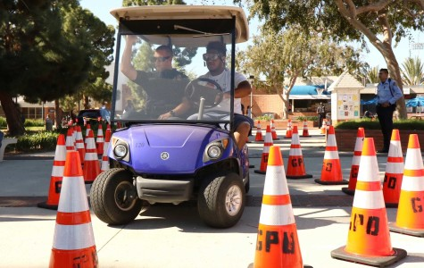 Joseph Taliauli, 19 kinesiology major puts on beer goggles, which simulates being drunk at the legal limit of .08. He then tries to navigate through a course of cones with ECPD officer Matt Ryan during the 15th Annual South Bay DUI Awareness Fair on Thursday.  Photo credit: Jackie Ramano