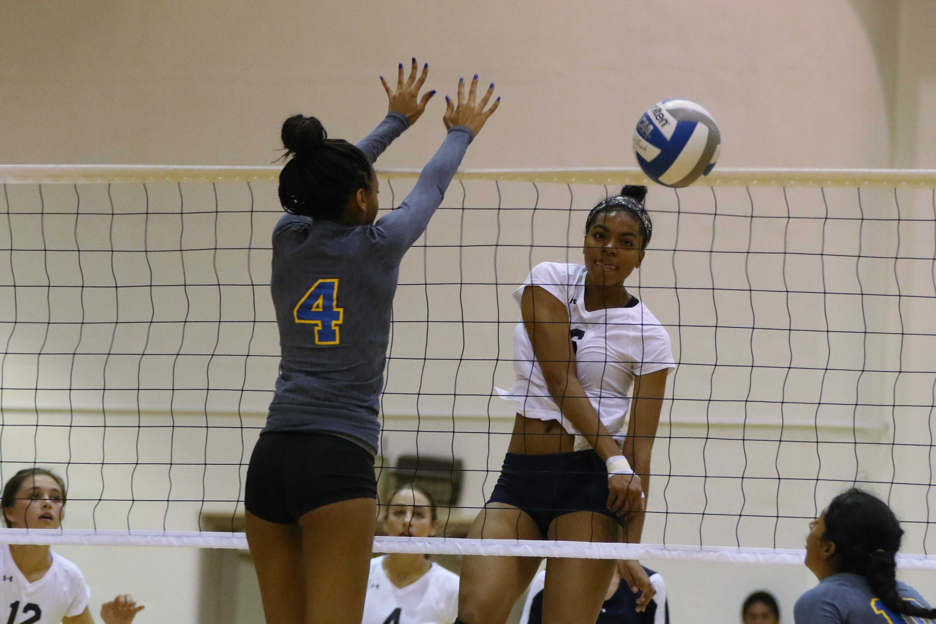 Warriors' sophomore outside hitter Kezia Boyer spikes the ball through the Hornets' Kaylyn Johnson during the first game of the playoffs on Tuesday, Nov. 24. Photo credit: Jo Rankin