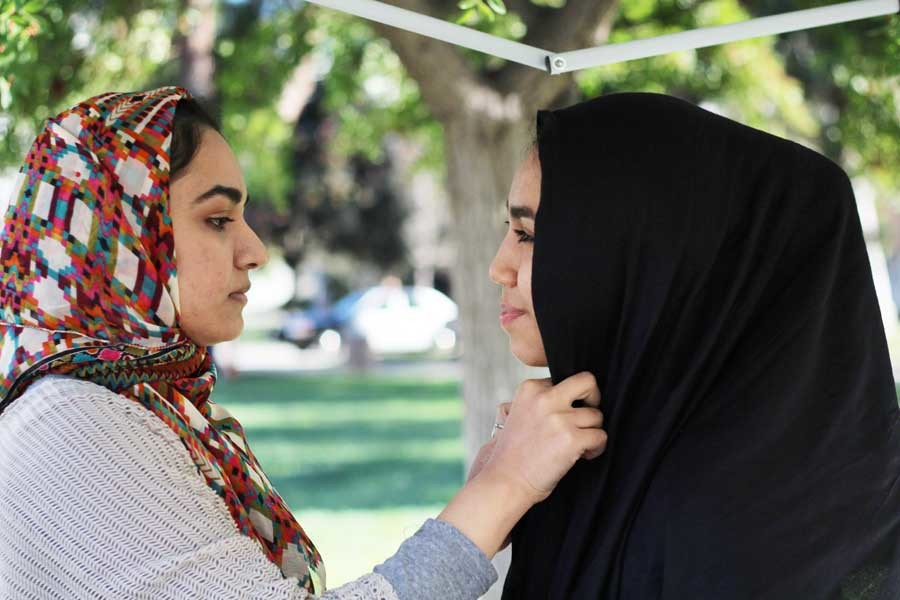 Zirwa Kainat, 20, biology major puts a hijab on Angie Rivera, 19, history major during Hijab Day on Thursday, Nov. 5. The Muslim Student Association hosted Hijab Day to educate students on the Islamic headscarf and to challenge women to wear it for the day and then report back on their experience. Photo credit: Jo Rankin