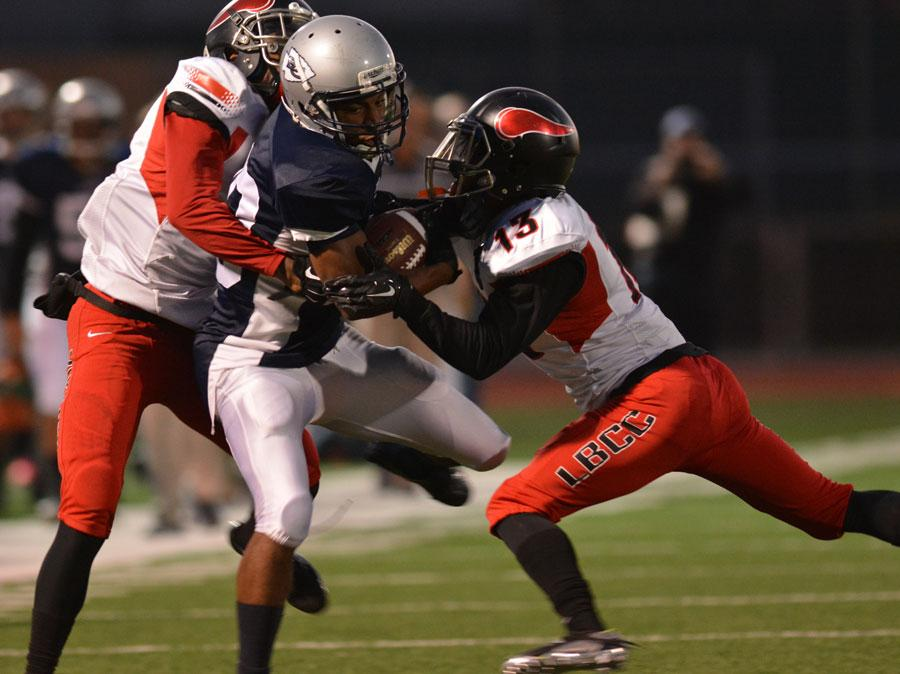 Warriors wide receiver William Morehand get tackled by Long Beach City College defensive backs Kiante Goudeau and Chazz Sanders during the first quarter on Saturday night. The Warriors lost to the Vikings 38-36 in the last game of the season. Photo credit: John Fordiani