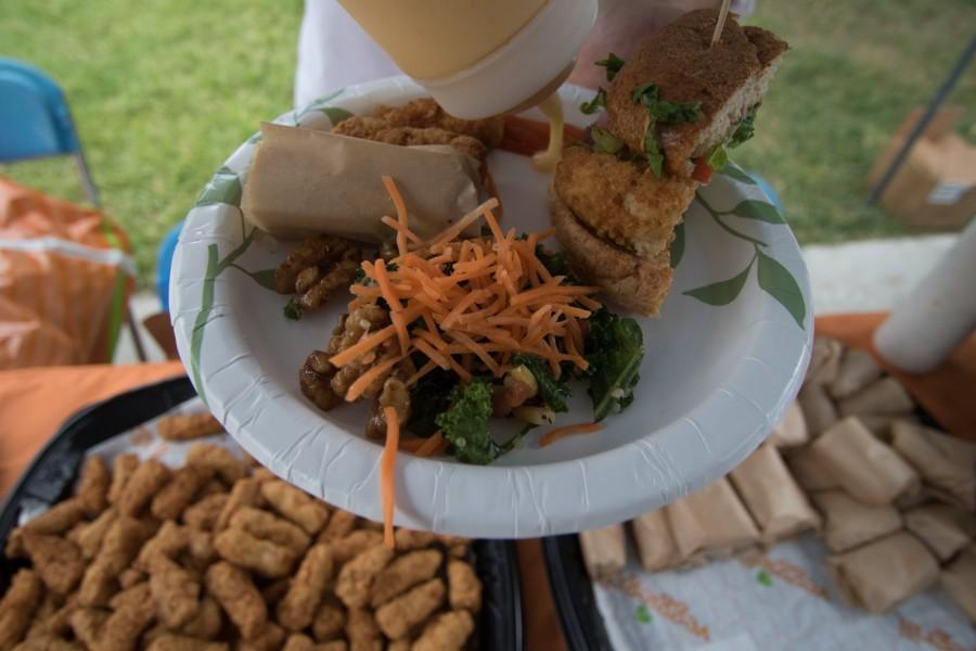 A Veggie Grill employee served sweet sauce on the plate alongside a buffalo mini wrap, all hail kale salad, santa fe crispy chicken sandwich and chill out wings from the restaurant at the Vegan Day Festival, in front of the Library Lawn. The Vegan Day Festival promoted vegan lifestyles in order to enlighten students about the abuse animals endure. Photo credit: Jorge Villa
