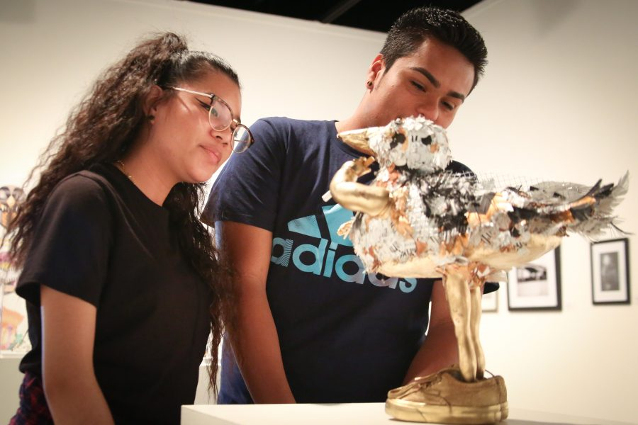 "Bryan Chavez, 19, psychology major (left), with Dianelly Santos, 20, sociology major, examine the art piece ""Steven Seagull"" by Clara Hana Kwon in the art gallery on April 18. Photo credit: Sue Hong"