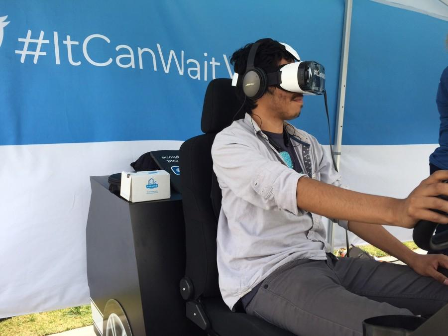 Milton Roa, 19, engineering major, participates in AT&T's It Can Wait campaign while wearing virtual reality goggles showing the dangers of texting and driving. AT&T representatives brought a simulator to campus to show students the dangers of texting and driving. Photo credit: John Fordiani