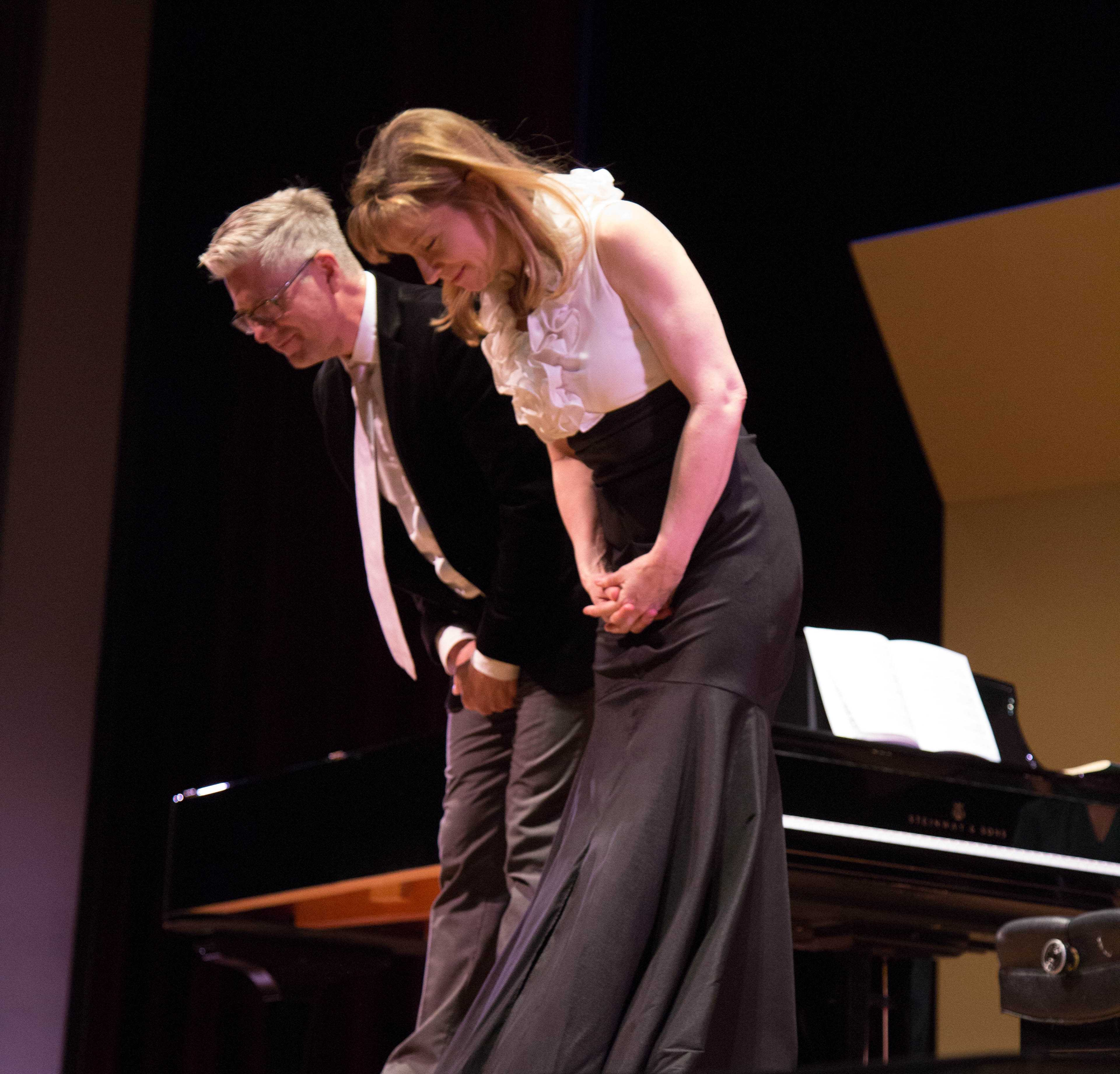 Pianists Christopher Brennan and Polli Chambers-Salazar take a bow after the performance of their last song