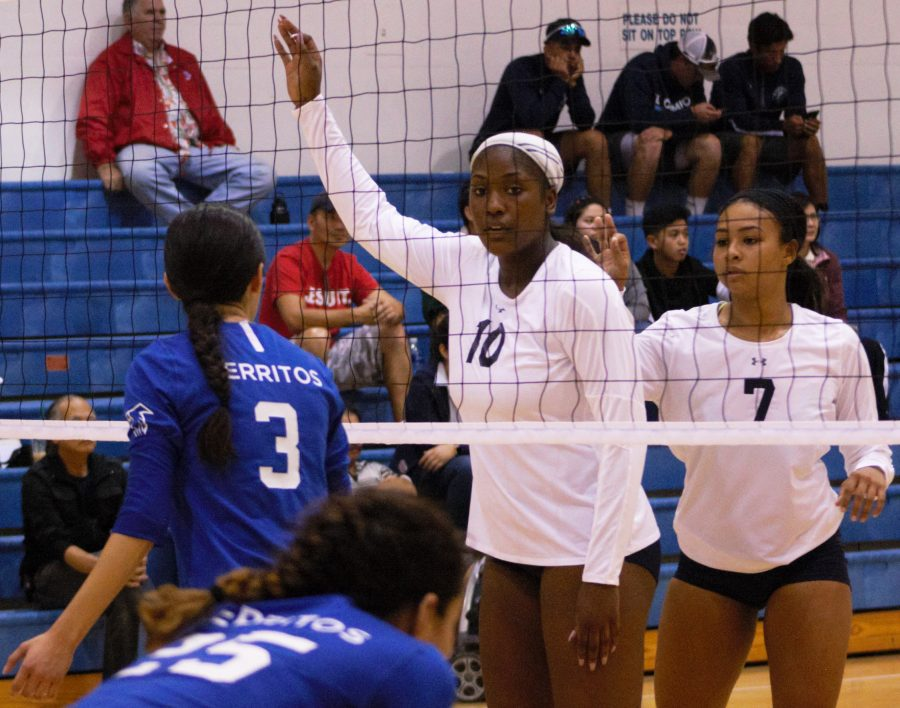 El Camino women's volleyball freshman middle blocker Cheyanne Smith (white No. 10) and freshman outside hitter Aiko Waters (white No. 7) wait for the serve against the Cerritos College Falcons on Wednesday night. EC Warriors would win in straight sets (29-27, 25-19, 25-16). Photo credit: Alain Miranda