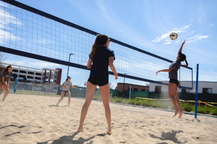 Sophomore Michelle Shimamoto attacks the ball during practice against sophomore Nina Wyer and freshman Melissa Euyoque, while freshman partner Micah Hammond looks on. Shimamoto and Hammond make up the No. 1 beach volleyball pair for the El Camino Warriors. Photo credit: Jorge Villa