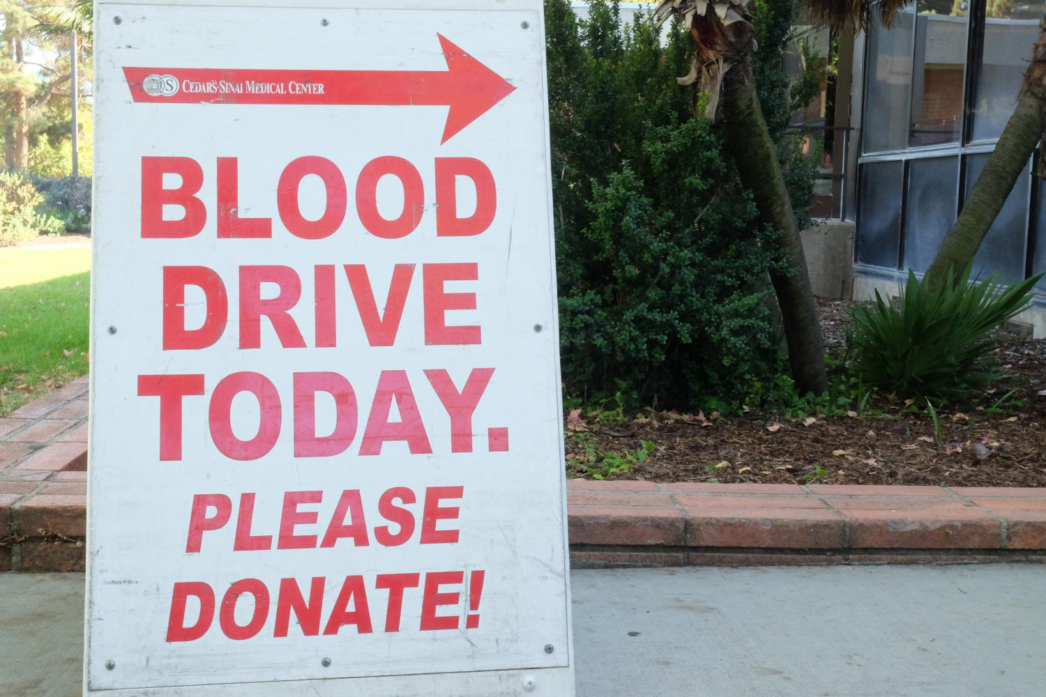 A sign indicating where the Cedars-Sinai blood drive is located, standing near the Student Activities Center. Photo credit: Emma Dimaggio