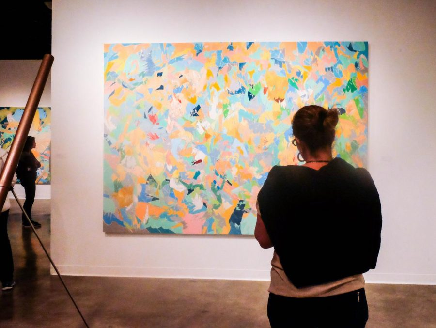 An+attendee+of+the+Centrifugal+Force+reception+looks+at+one+of+Tom+Jenkins%27+colorful+abstract+paintings.+Photo+credit%3A+Emma+DiMaggio