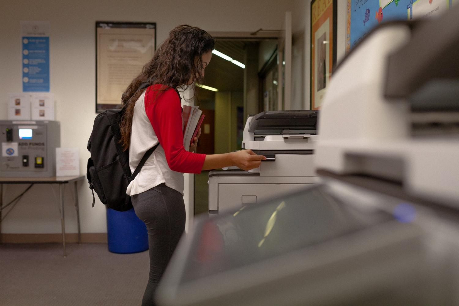Liliana Garcia, 19, administration justice major is swiping her ECC ID on the newly installed copier system on the main floor of the Schauerman Library. Garcia is printing a test she recieved via email from her professor.