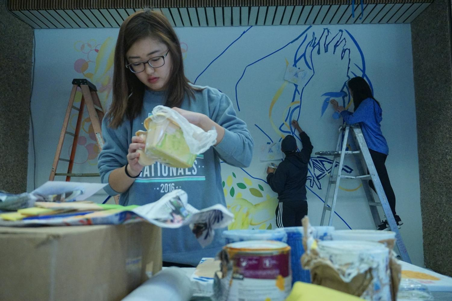 Haruka Kanemura ,19, studio art major, and her team painting a mural in the East Lounge of the Student Activities Center. Photo credit: Ryan Guitare