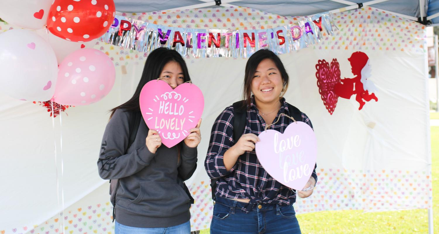 Students pose with props at the photo booth set up by the Financial Aid Office at the Fall in Love with Financial Aid fair on Tuesday, Feb. 13. Photo credit: Emma DiMaggio