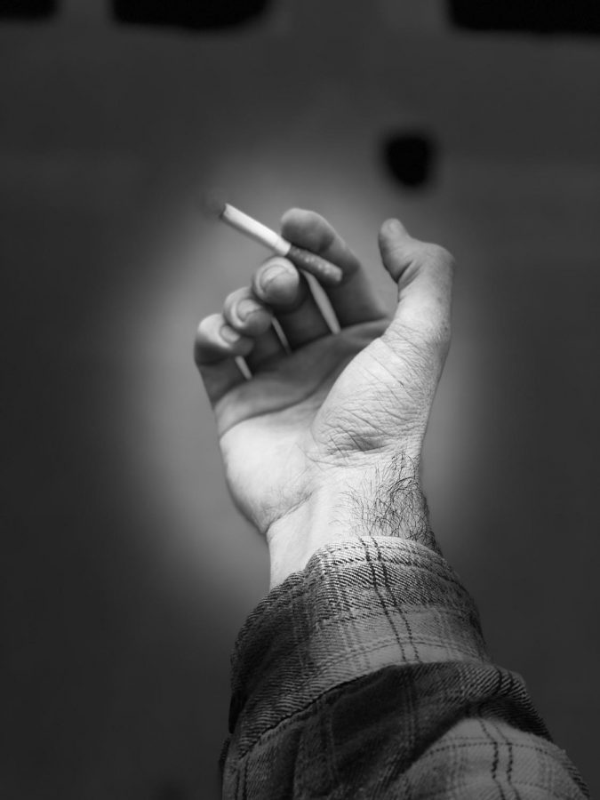 A photo illustration of a student smoking a cigarette on campus. Photo credit: Ryan Guitare