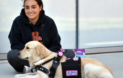 Dani poses with her service dog Luca in front of the Humanities Building. Photo by Jack Kan.