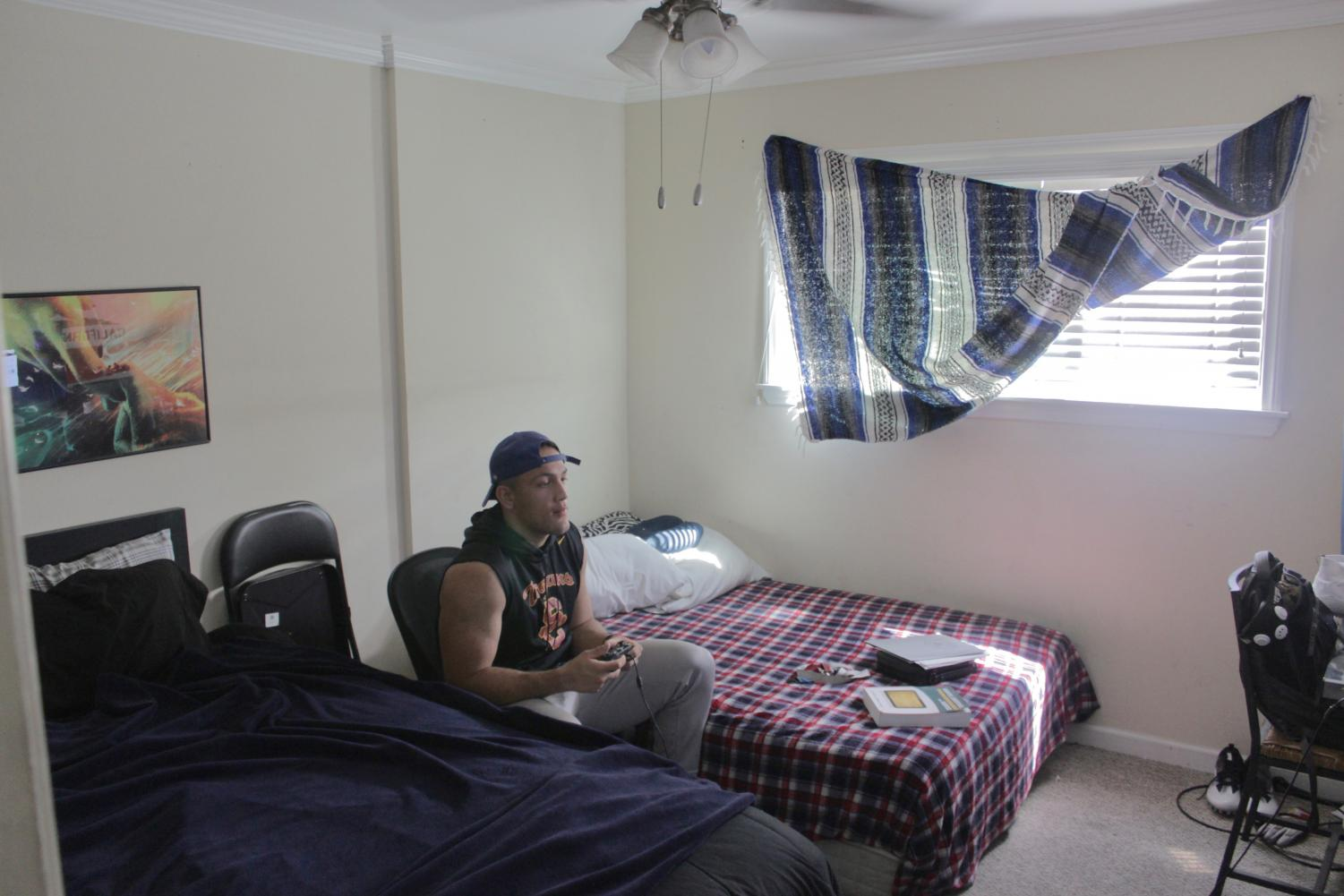 Jaymin Austin, 21 relaxes in his room playing a few rounds of Fortnite. Photo credit: Jeremy Taylor