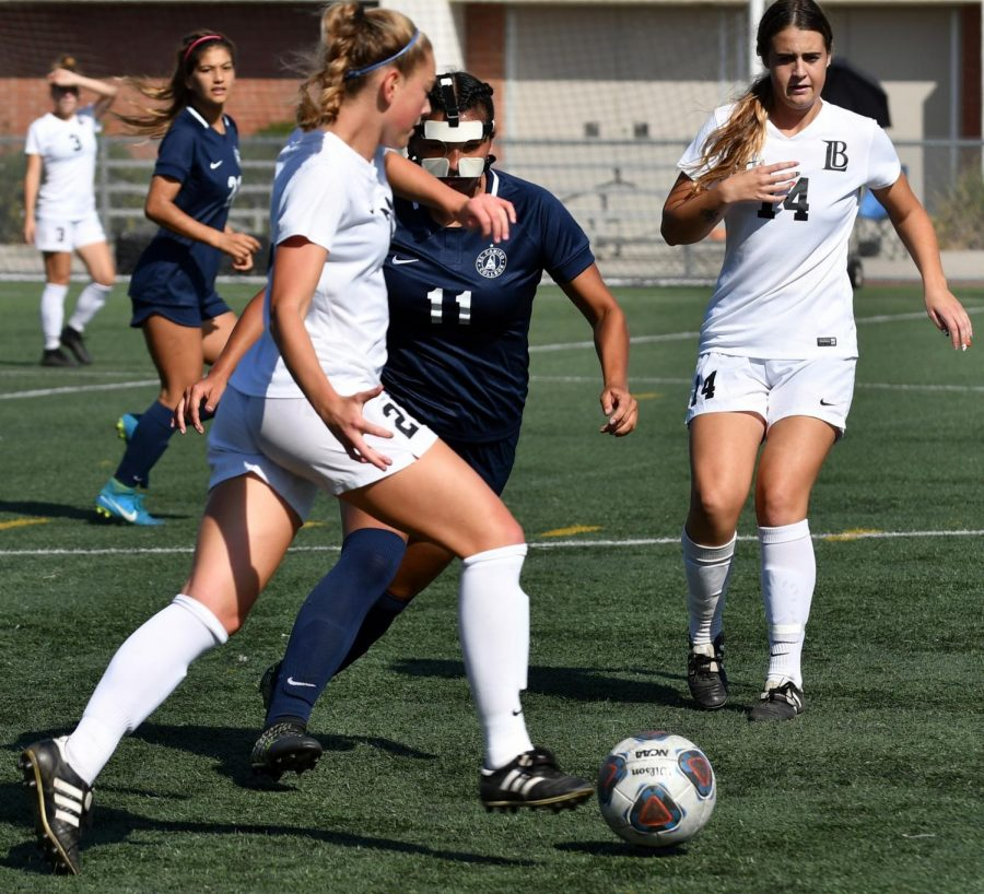 EC forward Nalleli Mendoza (No.11) battles for the ball against Long Beach City College at home on Friday, Oct. 26. She is wearing a mask because her nose was broken in a previous match. Photo credit: Jack Kan