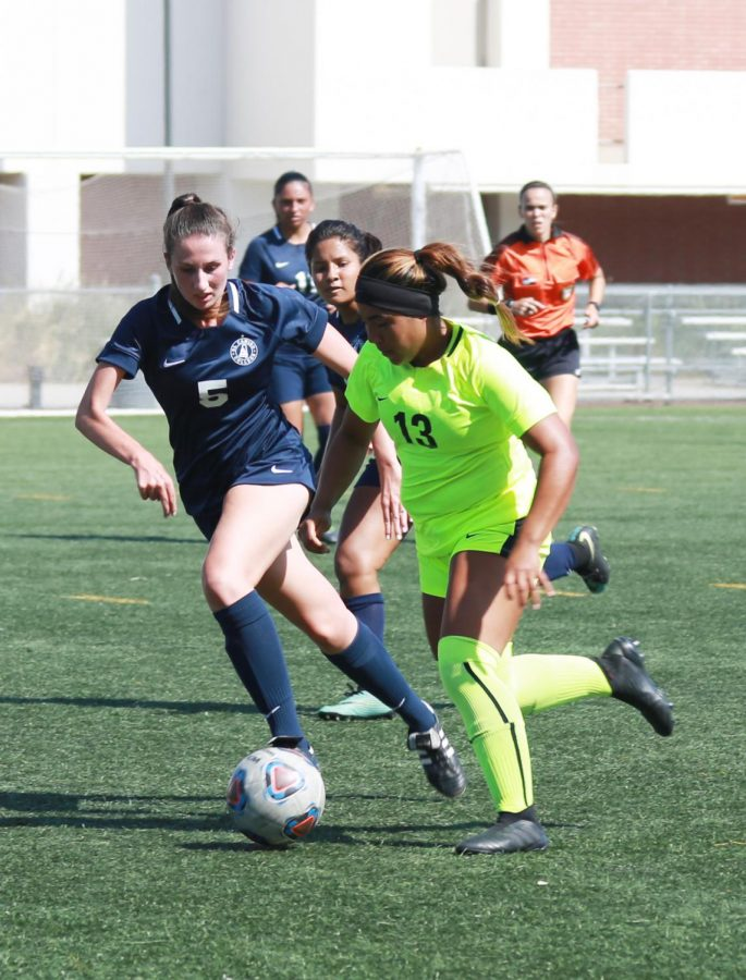 ECC defender Erica Holcombe (No.5) keeps the pace with Seahawks player at El Camino vs LA Harbor women's soccer game on Friday, Sept. 28, at ECC. Photo credit: Mari Inagaki