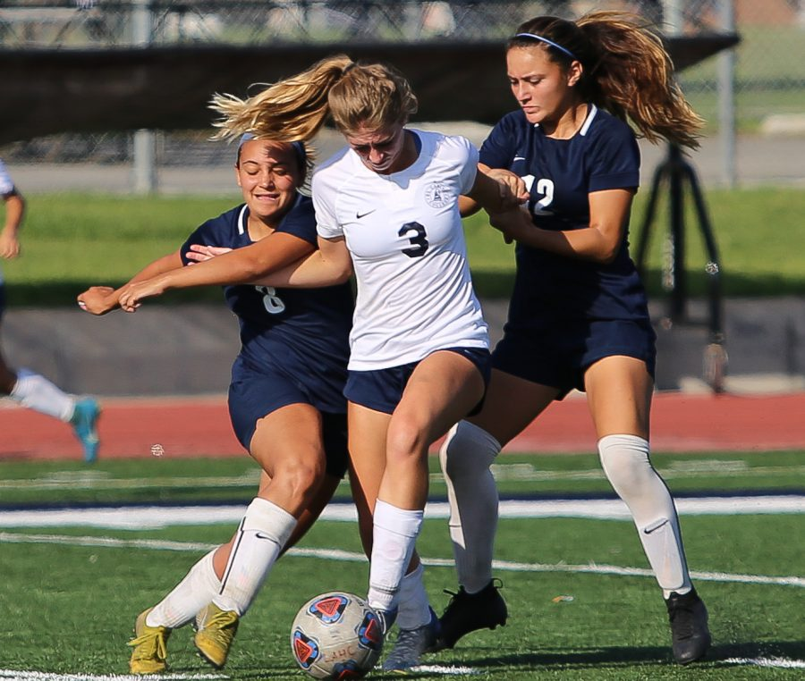 EC Warriors forward, Robin Riggs (No. 3), fights to free herself from two Harbor players, during the EC Warriors vs Harbor College Seahawks women's soccer match held at Harbor College Tuesday, Oct. 30. Photo credit: Darwyn Samayoa
