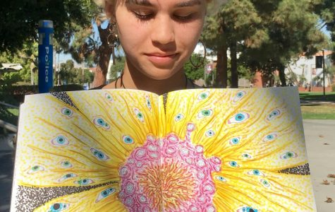 Multi-talented artist, Jackie Robinson, shows off one of her drawings by the art quad on Tuesday, Nov. 9. Photo credit: Arielle Chacon