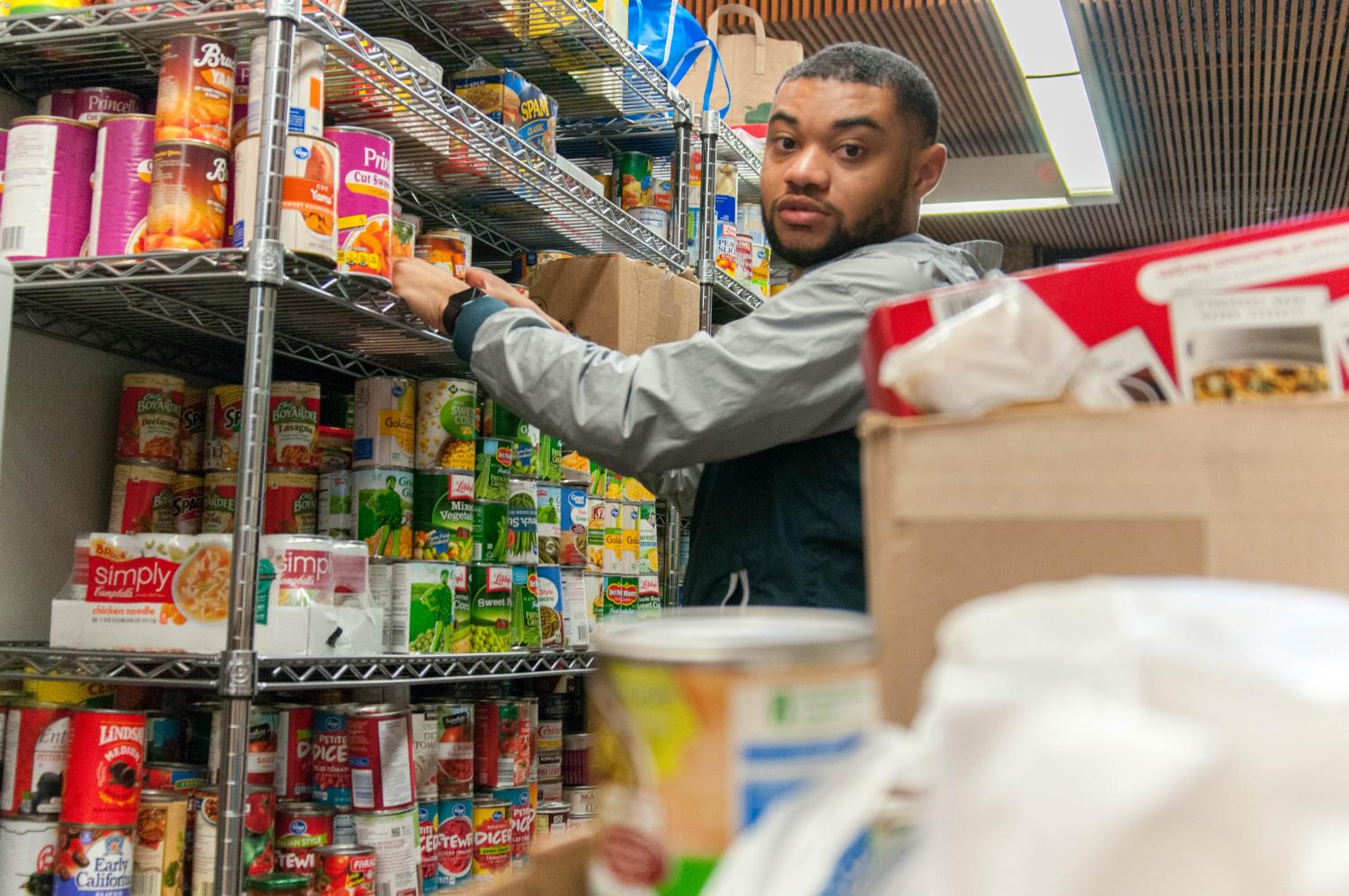 Isaiah Robinson, 20, Computer Science/ Business, stocks up the Warrior shelves with food donations. Photo credit: Elena Perez