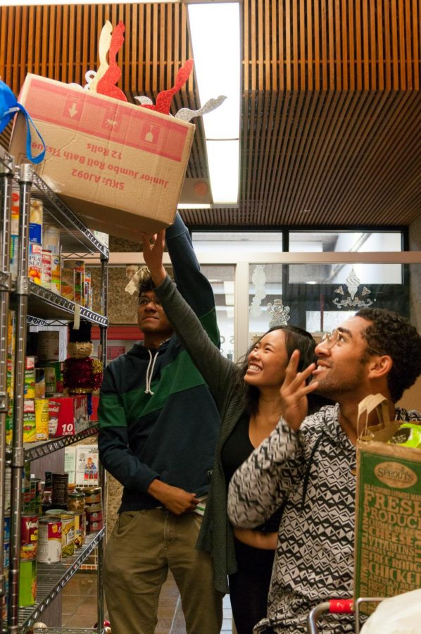 Norman Xavier, 18, Political Science, Lindsey Lee, 18, Business, and Sean Min, 20, Architecture, members from the student body help organise donations in the ASO executive office pantry. Photo credit: Elena Perez