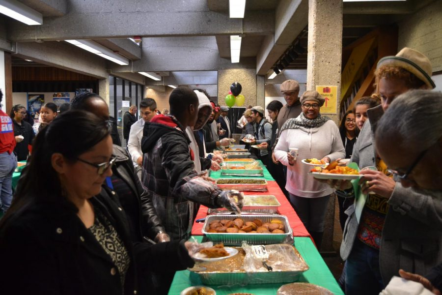 Students, faculty, and staff smiling as they collect their soul food as part of the