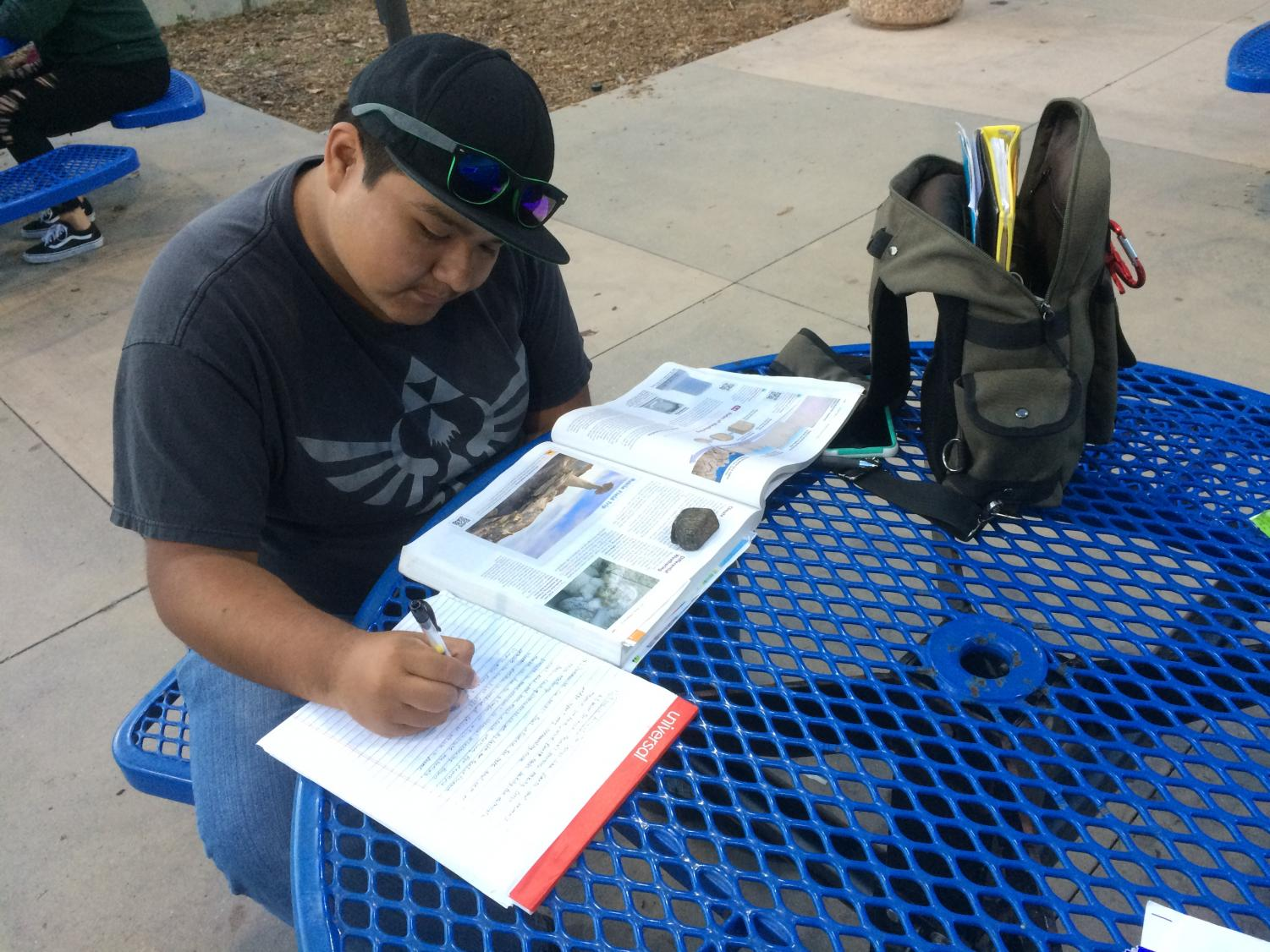 Student worker for the Special Resource Center, Eric Palma, 21, is busy near the Cafe Camino doing his academic work to succeed as a geology major.