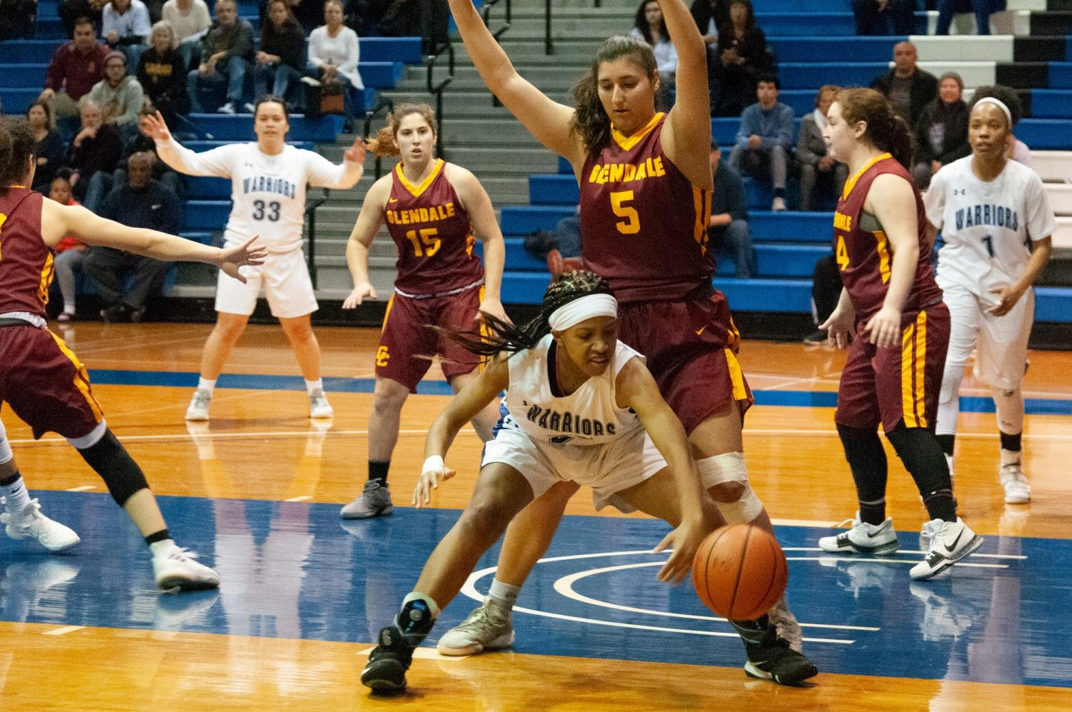 Alexia Mason (No. 21) of the women's basketball team keeps possession alive for the Warriors during their playoff game versus Glendale on Friday, March 1 at the ECC North Gym. Photo credit: Elena Perez