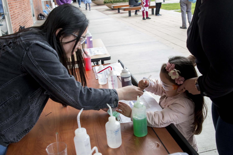 Student Natalie Okamura, pre-nursing major, helps participant Vianey Cardenas, preschool, makes squishy polymers at the science courtyard. March 9, 2019. Photo credit: Mona Itani