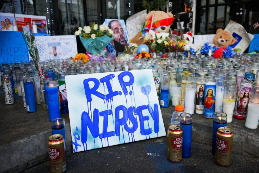 Several candles cover the parking lot of the South LA plaza on Wednesday, April 3. Fans of Nipsey Hussle continue to gather around his store The Marathon Clothing to pay their respects. Photo credit: Jun Ueda